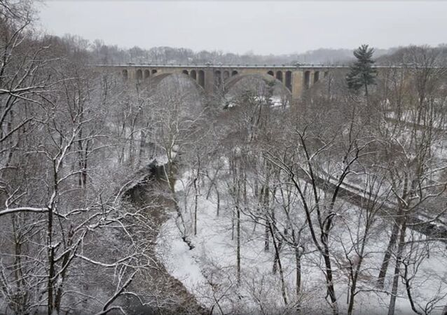 Image of the Taft Bridge in Washington, DC, captures snow-covered greenery in Rock Creek Park as a massive snowstorm envelops much of the US East Coast.
