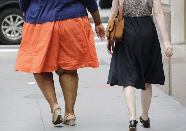 In this Monday, July 13, 2015 photo, an obese woman, left, walks in New York. One-third of American adults and one in six children are now obese, although an annual report released Thursday by two nonprofit groups found that rates could be stabilizing