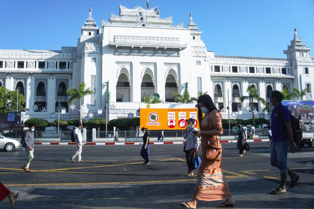 People walk past Yangon City Hall on 2 February 2021, a day after Myanmar's military seized power, detained democratically elected leader Aung San Suu Kyi and imposed a one-year state of emergency.