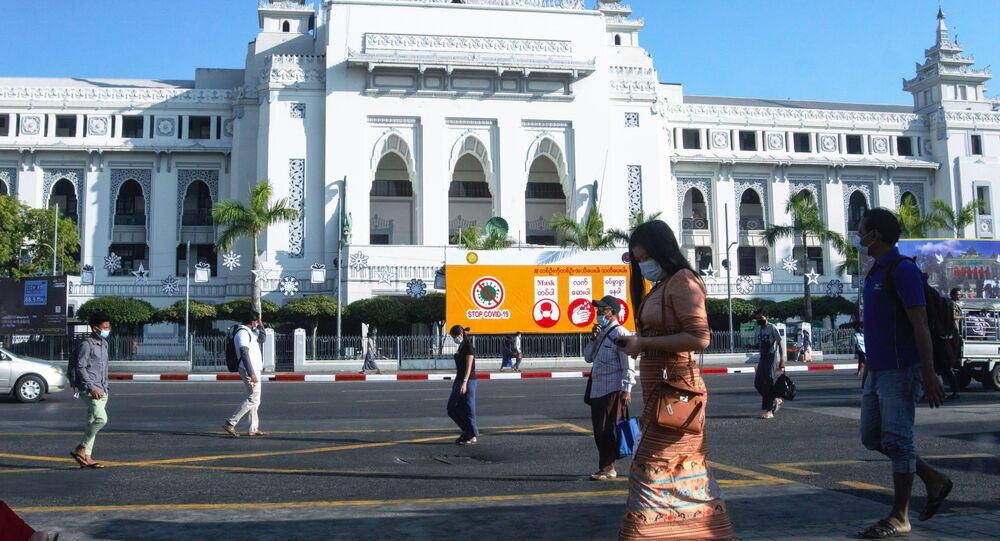 People walk past City Hall in Yangon on February 2, 2021, a day after Myanmar's military seized power in a bloodless coup, detaining democratically elected leader Aung San Suu Kyi and imposing a one-year state of emergency.