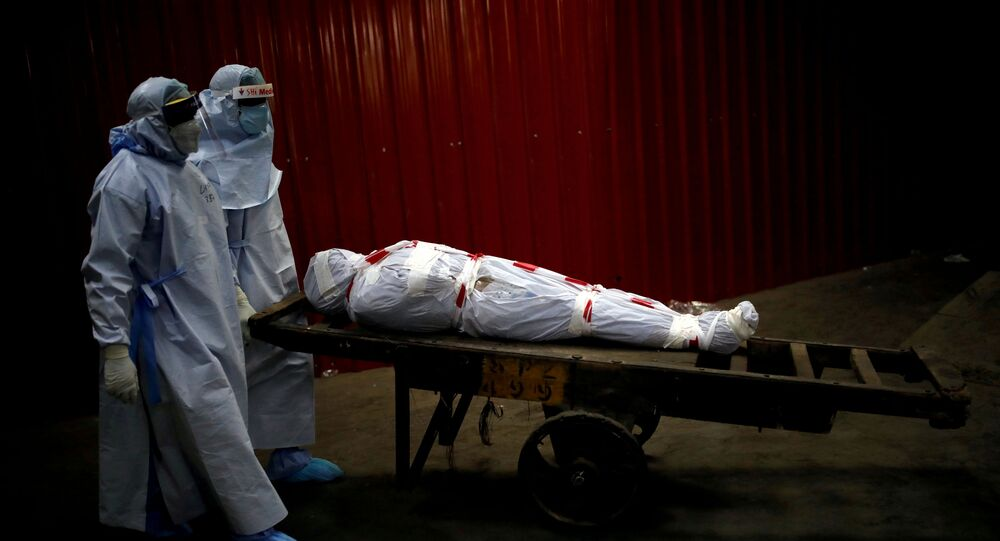 Health workers carry the body of a man who died from the coronavirus (COVID-19) to be cremated in New Delhi.