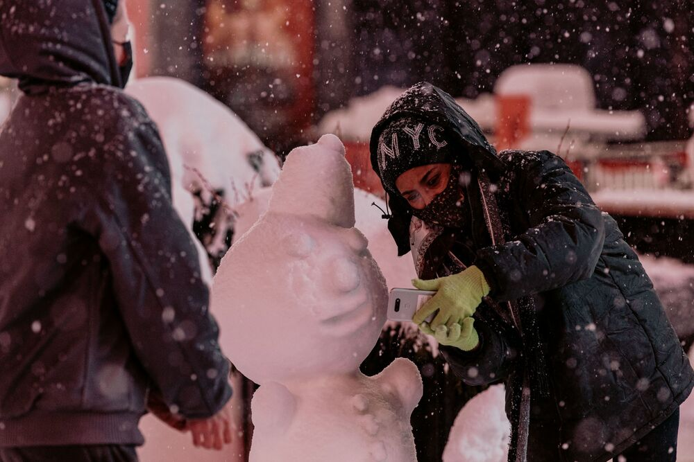 A woman poses for a photo as snow continues to fall in Times Square on 1 February 2021 in New York City. NYC Mayor Bill de Blasio declared a State of Emergency as a nor'easter brings blizzard-like conditions with up to 18 inches of snow into the city.