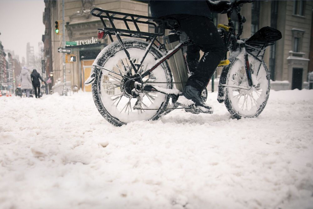 A bicycle food delivery worker rides through heavy snow that fell at a rate of several inches an hour on 1 February 2021, in the Soho neighbourhood of New York City after a nor'easter dumped nearly a foot-and-a-half of snow on the area.