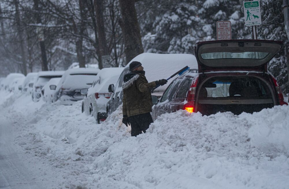 A man cleans a car during in Weehawken, New Jersey on 1 February 2021. A powerful winter storm is dumping snow along a stretch of the US east coast including New York City on 1 February 2021, after blanketing the nation's capital.