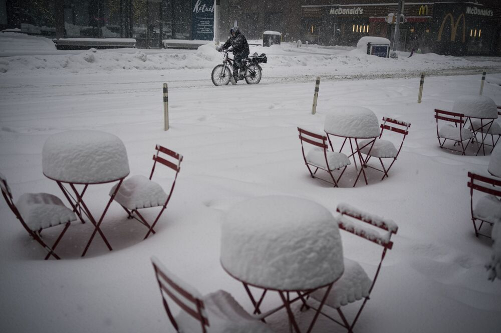 A man delivers food on his electric bicycle as he rides past snow-covered dining tables in midtown during a snowstorm, Monday, 1 February 2021, in New York.