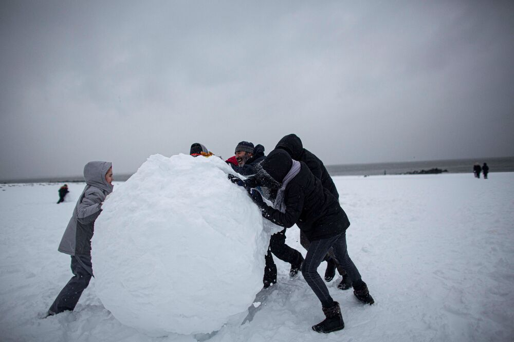 People make a giant snow ball during a winter storm at Brighton Beach, New York, U.S., 1 February 2021.