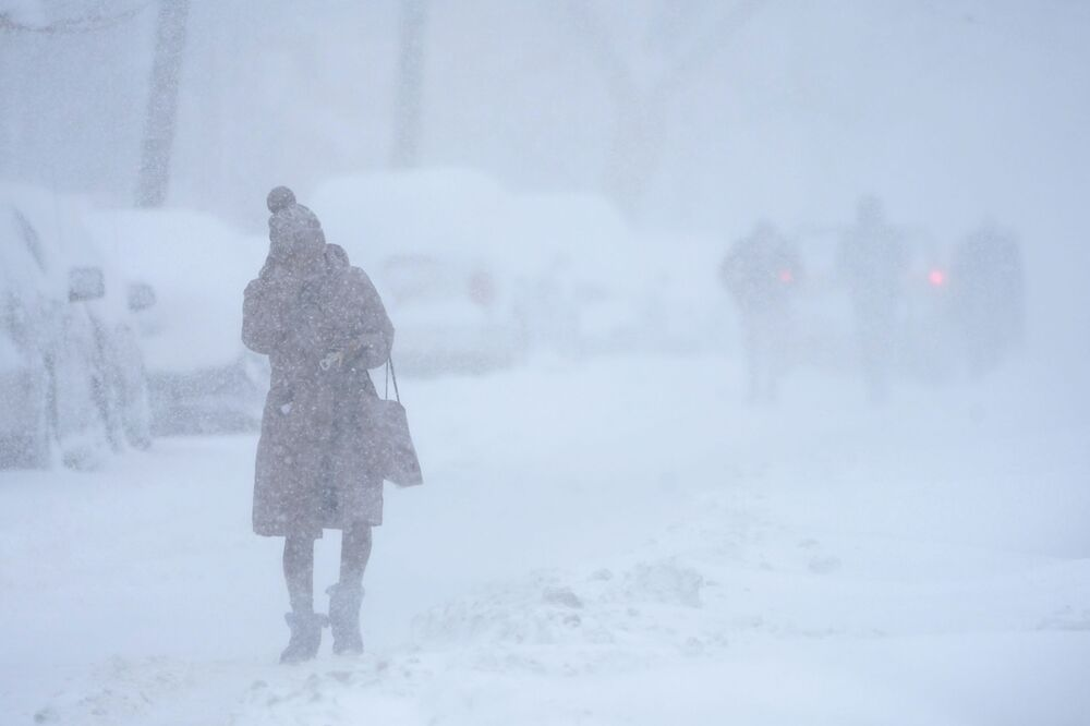 A woman tries to protect her face while walking in white-out conditions in Jersey City, N.J., 1 February 2021. A sprawling, lumbering winter storm is walloping the Eastern U.S., shutting down coronavirus vaccination sites, closing schools and halting transit. With snow falling since Sunday evening, New York City and northern New Jersey braced for as much as 22 inches of snow, and parts of New England for a foot or more.