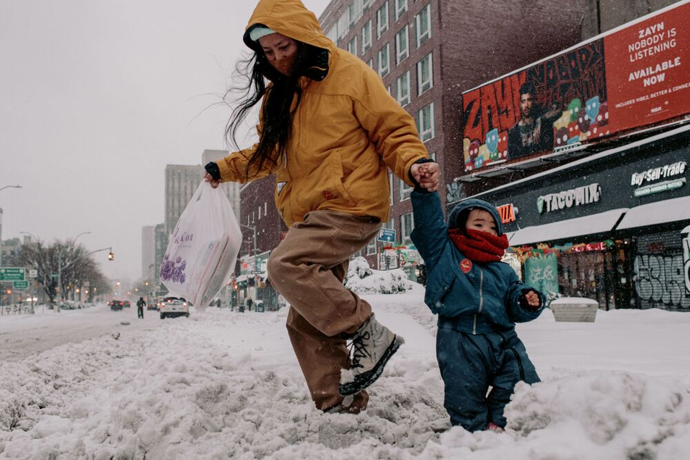 People walk through snow-covered streets along Manhattan on 1 February 2021 in New York City. NYC Mayor Bill de Blasio declared a State of Emergency as a nor'easter is expected to bring blizzard-like conditions with up to 18 inches of snow into the city.