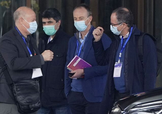 Peter Ben Embarek, right, gestures as Peter Daszak, left, approaches to bump fists with him before they leave the hotel with other members of a World Health Organization team for another day of field visit in Wuhan in central China's Hubei province Tuesday, Feb. 2, 2021