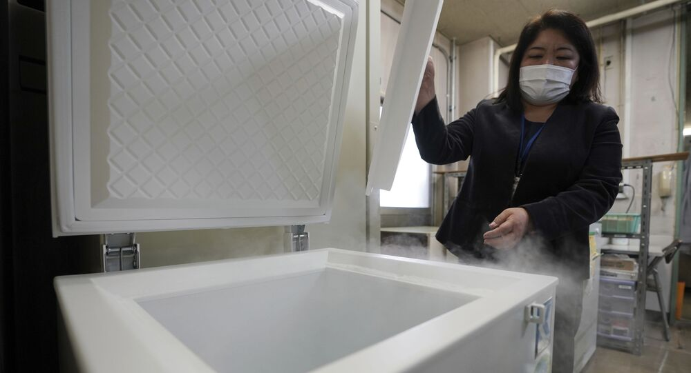 A local health staff shows a special freezer for COVID-19 vaccinations at Tokyo's Sumida ward office Friday, Jan. 22, 2021. Japan is accelerating preparations for COVID-19 vaccinations in hopes of starting them in late February, but uncertainty is growing as the country faces vaccine-shy public, slow approval process and bureaucratic roadblocks, casting a doubt if Tokyo Olympic this summer is possible.