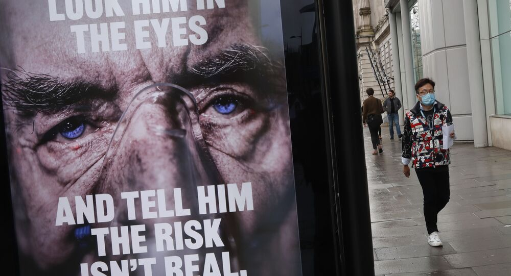 A man wearing a mask against coronavirus walks past an NHS advertisement about COVID-19 in London, Tuesday, Feb. 2, 2021.
