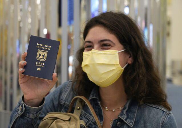 In this Nov. 26, 2020 file photo, an Israeli passenger from a flyDubai flight from Tel Aviv, Israel, waves her Israeli passport on arrival at Dubai International Airport's Terminal 3 in Dubai, United Arab Emirates.