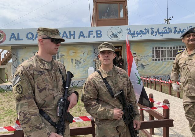 In this March 27, 2020 file photo, U.S. soldiers stand guard during the hand over ceremony of Qayyarah Airfield, Iraqi Security Forces, in the south of Mosul, Iraq.