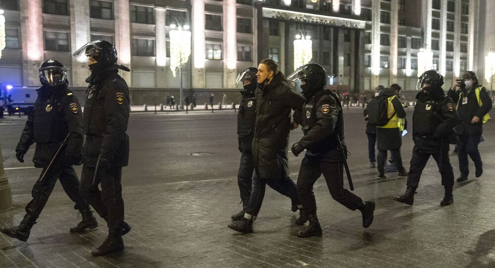 Police detain a man, with the the State Duma, the Lower House of the Russian Parliament, in the background in Moscow, Russia, Tuesday, Feb. 2, 2021.