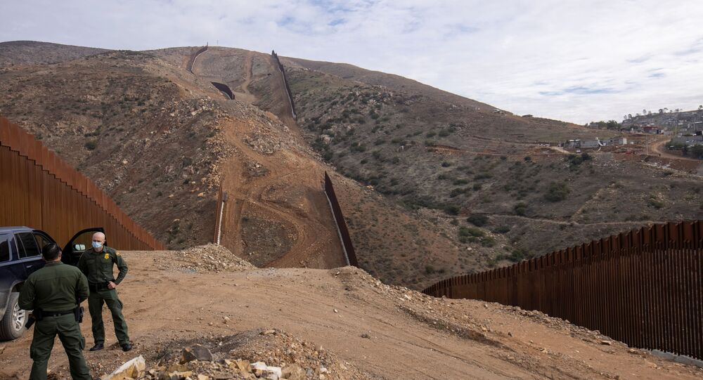 U.S. border patrol agents stand near the location of halted construction along the U.S. Border wall with Mexico as an unfinished  section is shown on Otay Mountain, east of San Diego, California, U.S., February 2, 2021.