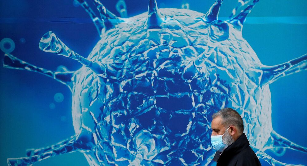 FILE PHOTO: A man wearing a protective face mask walks past an illustration of a virus outside a regional science centre amid the coronavirus disease (COVID-19) outbreak, in Oldham, Britain 3 August 2020.
