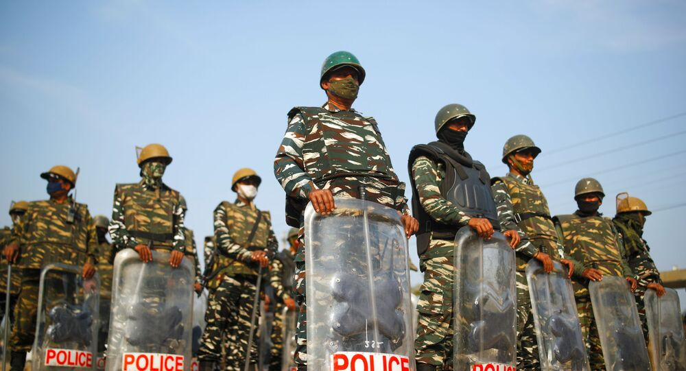Police officers in riot gear stand guard at the site of a protest against the farm laws at Singhu border in New Delhi