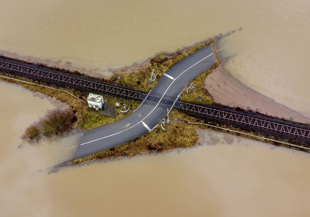 A railroad crossing is surrounded by flooding caused by rain and melting snow in Nidderau near Frankfurt, Germany, Wednesday, 3 February 2021.