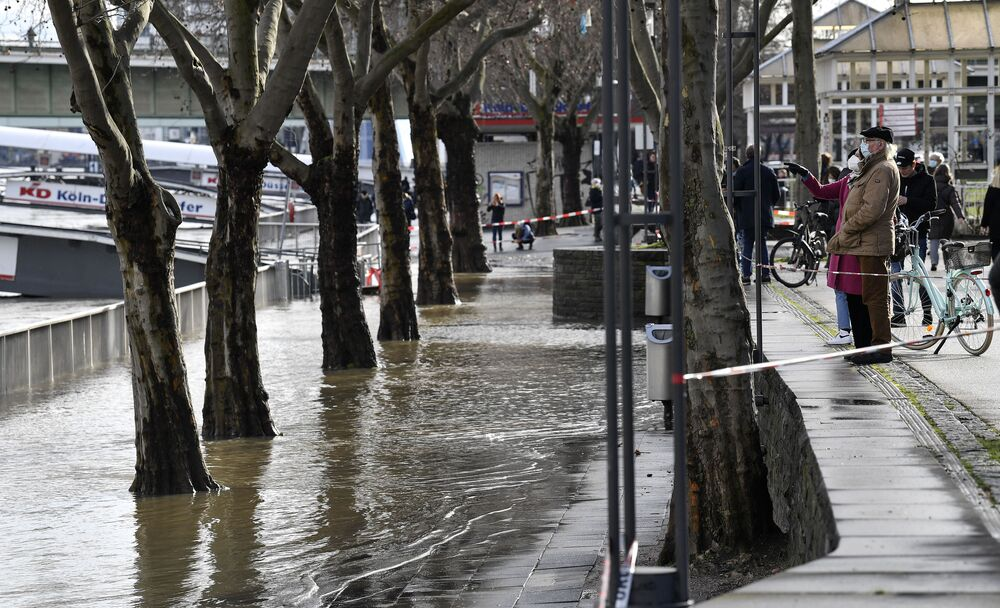 People view a flooded promenade near the Rhine River in Cologne, Germany, Wednesday, 3 February 2021. High tides caused by rain and melting snow are threatening commercial shipping on Germany's biggest river, the Rhine.