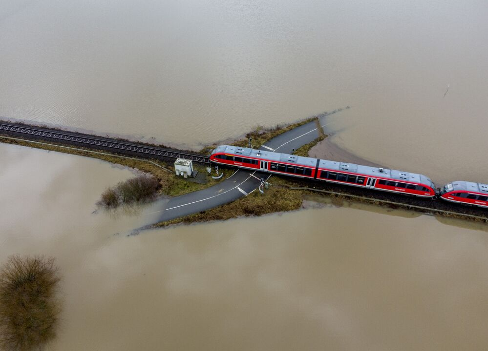 A train passes a railroad crossing that is surrounded by flooding caused by rain and melting snow in Nidderau near Frankfurt, Germany, Wednesday, 3 February 2021.