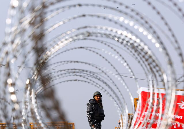 Police officer in riot gear stands guard behind concertina wire at a protest against farm laws at the Delhi-Uttar Pradesh border in Ghaziabad, India
