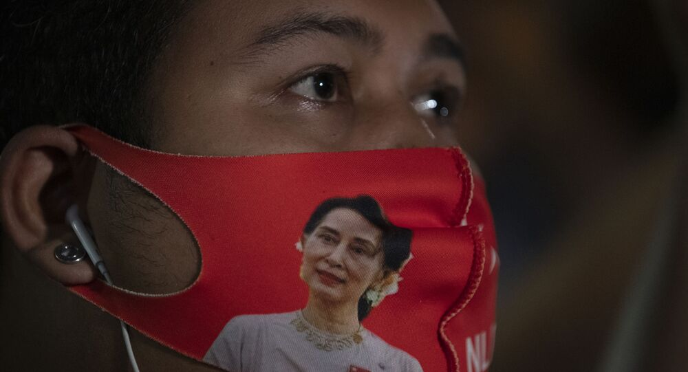 A Myanmar national living in Thailand wears a face mask with the image of Myanmar leader Aung San Suu Kyi during a protest in front of Myanmar Embassy in Bangkok, Thailand, Thursday, Feb. 4, 2021. The military announced Monday that it will take power for one year, accusing Suu Kyi's government of not investigating allegations of voter fraud in recent elections. Suu Kyi's party swept that vote and the military-backed party did poorly. The state Election Commission has refuted the allegations.