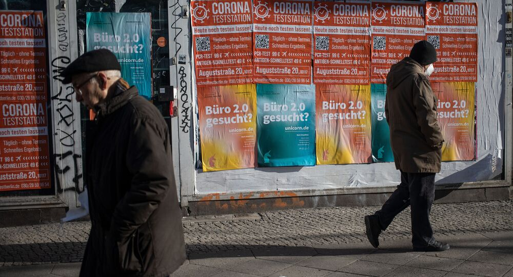 People walk past a closed shop front with posters advertising a Corona test centre in Berlin's Kreuzberg district on February 1, 2021 amid the ongoing coronavirus COVID-19 pandemic.