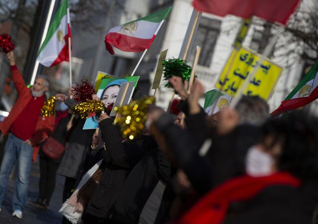 People wave flags and confetti after the trial of four persons, including an Iranian diplomate and Belgian-Iranian couple at the courthouse in Antwerp, Belgium, Thursday, Feb. 4, 2021.