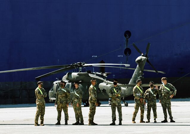 Members of U.S forces stand backdropped by a military helicopter and the U.S. troop carrier Endurance, in the northeast Greek port of Alexandroupolis, near the Turkish border, Thursday, July 23, 2020, where some 2,000 U.S. service members, dozens of helicopters and hundreds of vehicles disembarked