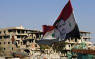 In this July 15, 2018 file photo, a Syrian national flag with a picture of Syrian President Bashar Assad flies at an Army check point, in the town of Douma in the eastern Ghouta region, near Damascus, Syria.