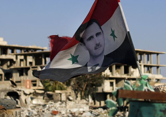 In this 15 July 2018 file photo, a Syrian national flag with a picture of Syrian President Bashar Assad flies at an Army checkpoint in the town of Douma in the eastern Ghouta region, near Damascus, Syria.
