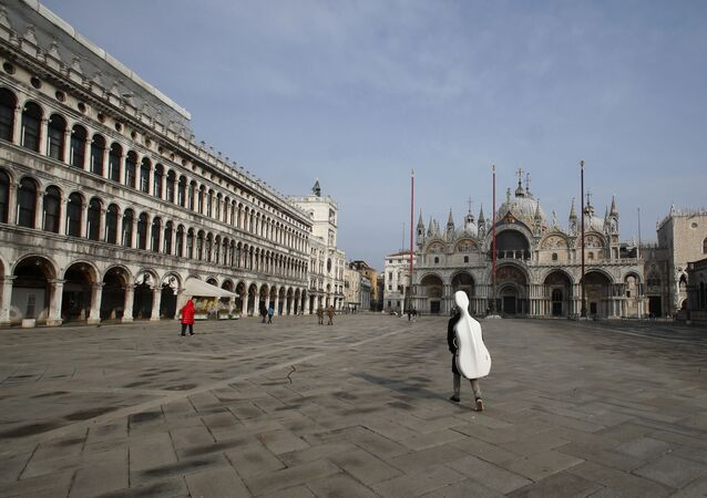 A young man walks in an empty St. Mark's Square in Venice, Italy, Saturday, Jan. 30, 2021. Gondolas and other vessels are moored instead of preparing for Carnival's popular boat parade in the lagoon. Alleys are eerily empty. Venetians and the city's few visitors stroll must be masked in public places, indoors and out, under a nationwide mandate.