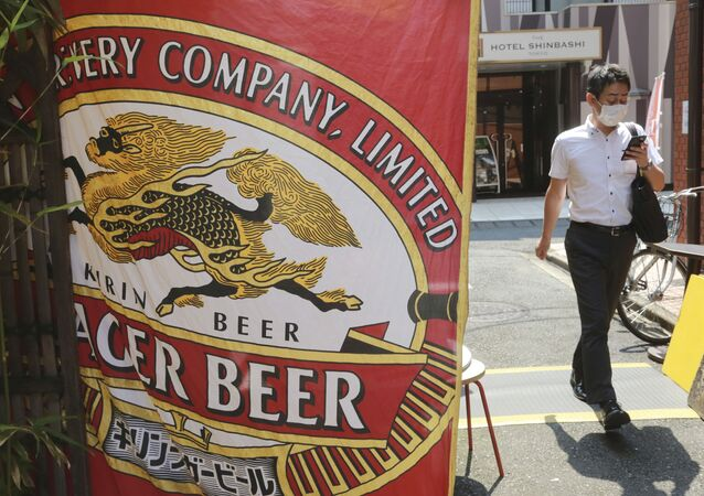 A man walks near an advertisement of a Kirin brand beer in Tokyo, Tuesday, Aug. 25, 2020. Australia's government announced on Tuesday it proposed to block Kirin Holdings Co.'s 45.6 billion yen ($430 million) sale of its Australian beverage unit to a Chinese company in a development likely to increase strain on Chinese-Australian relations.