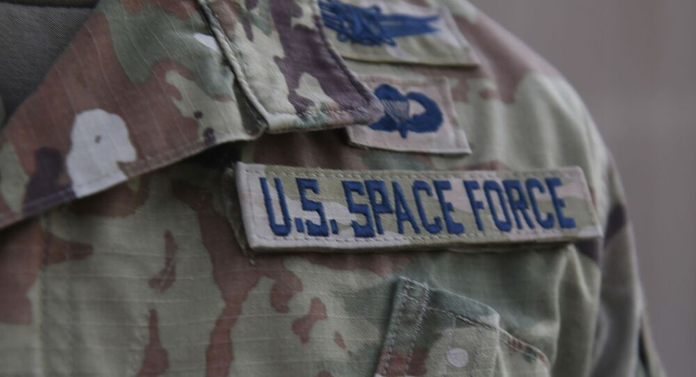 In this photo released by the U.S. Air Force, Capt. Ryan Vickers stands for a photo to display his new service tapes after taking his oath of office to transfer from the U.S. Air Force to the U.S. Space Force at Al-Udeid Air Base, Qatar, Tuesday, Sept. 1, 2020.