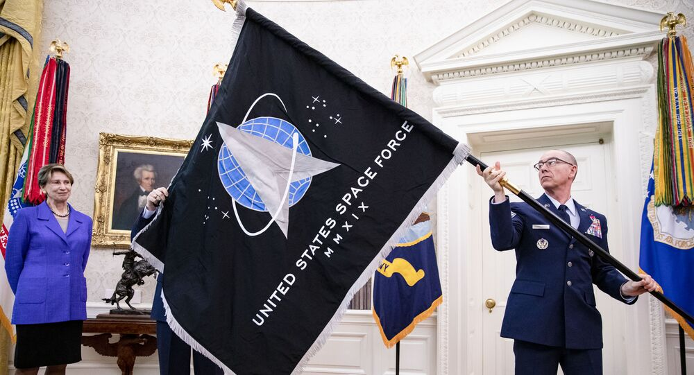 Chief Master Sgt. Roger Towberman (R), Space Force and Command Senior Enlisted Leader and CMSgt Roger Towberman (L), with Secretary of the Air Force Barbara Barrett present US President Donald Trump with the official flag of the United States Space Force in the Oval Office of the White House in Washington, DC on May 15, 2020.
