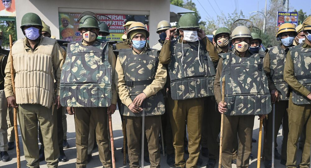 Police stand guard ahead of a roadblock protest called by farmers, part of their continuing demonstration against the central government's recent agricultural reforms, in Gurgaon on February 6, 2021.