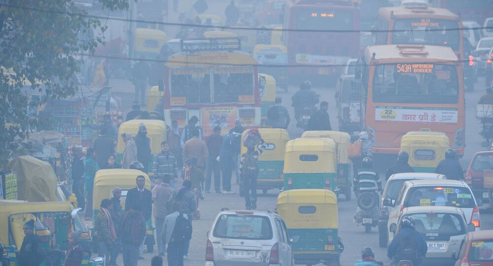 In this photograph taken on December 18, 2015, Indian commuters travel on a polluted road near a bus terminus in the Anand Vihar District of New Delhi.