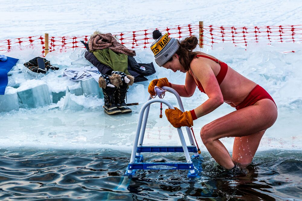 A member of the Submergents group comes out of 37.4°F (3°C) water after taking the plunge in a pool carved from the ice on Lake Harriet in Minneapolis, Minnesota, on 30 January 2021. Members meet up early every morning to plunge into the cold water for three minutes and some up to 17 minutes. The submergents say the practice has various health benefits.