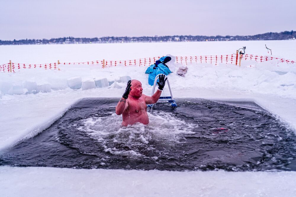 Bradley, a member of the Submergents group comes out of 37.4°F (3°C) water after taking the plunge in a pool carved from the ice on Lake Harriet in Minneapolis, Minnesota, on 30 January 2021. Members meet up early every morning to plunge into the cold water for three minutes and some up to 17 minutes. The submergents say the practice has various health benefits.