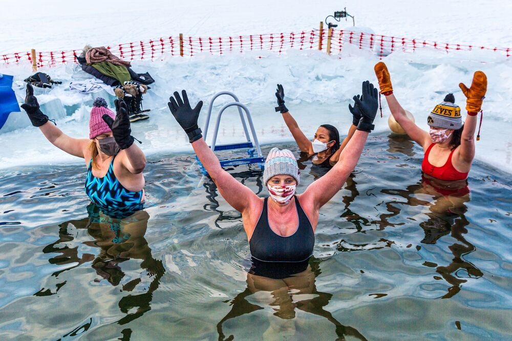 Members of the Submergents water after taking the plunge in a pool carved from the ice on Lake Harriet in Minneapolis, Minnesota, on 30 January 2021. Members meet up early every morning to plunge into the cold water for three minutes and some up to 17 minutes. The submergents say the practice has various health benefits.