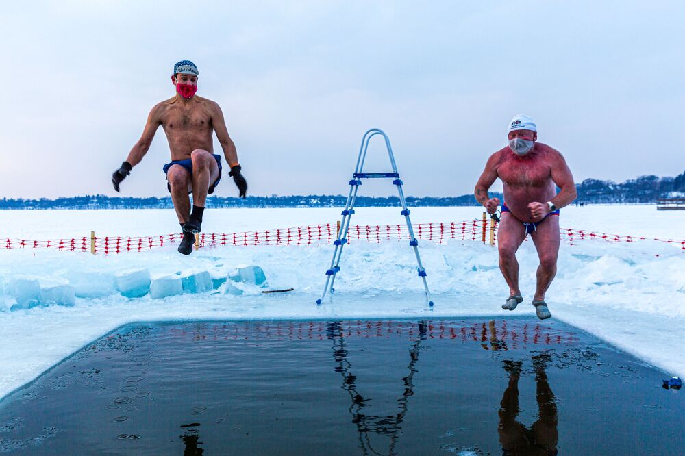 Nick (L) and Bradley (R), members of the Submergents group taking the plunge in a pool carved from the ice on Lake Harriet in Minneapolis, Minnesota, on 30 January 2021. Members meet up early every morning to plunge into the cold water for three minutes and some up to 17 minutes. The submergents say the practice has various health benefits.