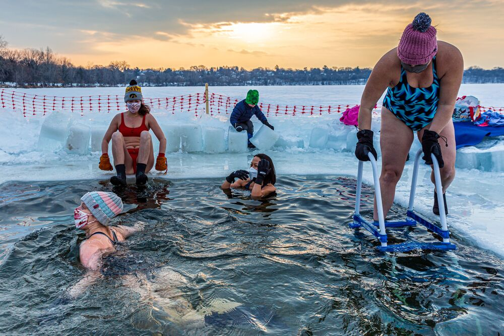 Members of the Submergents group swimming in a pool carved from the ice on Lake Harriet in Minneapolis, Minnesota, on 30 January 2021. Members meet up early every morning to plunge into the cold water for three minutes and some up to 17 minutes. The submergents say the practice has various health benefits.