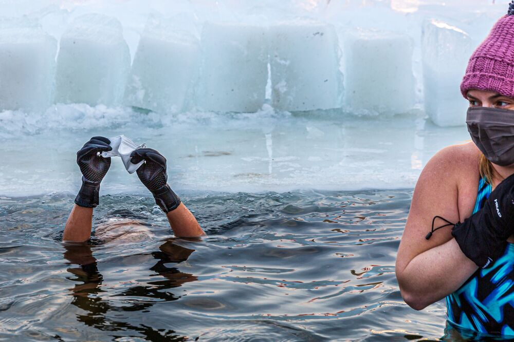 Members of the Submergents group take the plunge into 37.4°F (3°C) water in a pool carved from the ice on Lake Harriet in Minneapolis, Minnesota, on 30 January 2021. Members meet up early every morning to plunge into the cold water for three minutes and some up to 17 minutes. Submergents say the practice has various health benefits.