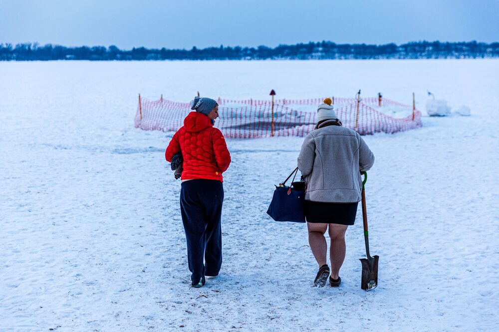 Members of the Submergents walk to the pool as they prepare to plunge into 37.4°F (3°C) water on Lake Harriet in Minneapolis, Minnesota, on 30 January 2021. Members meet up early every morning to plunge into the cold water for three minutes and some up to 17 minutes. Submergents say the practice has various health benefits.