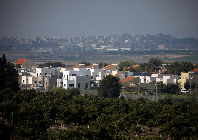 A general view shows an Israeli village in the foreground and part of the Gaza Strip, as it is seen from the Israeli side of the Israel- Gaza border, 6 February 2021. REUTERS/Amir Cohen