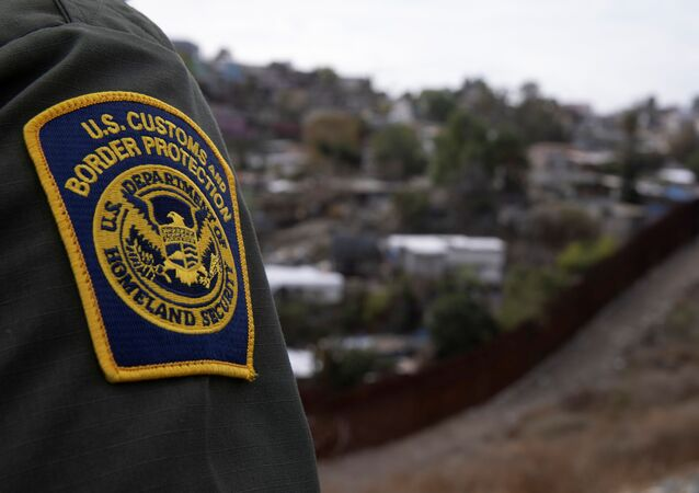 A US. border patrol agent looks out over Tijuana, Mexico from the US-Mexico border wall in San Diego, California, 2 February 2021.