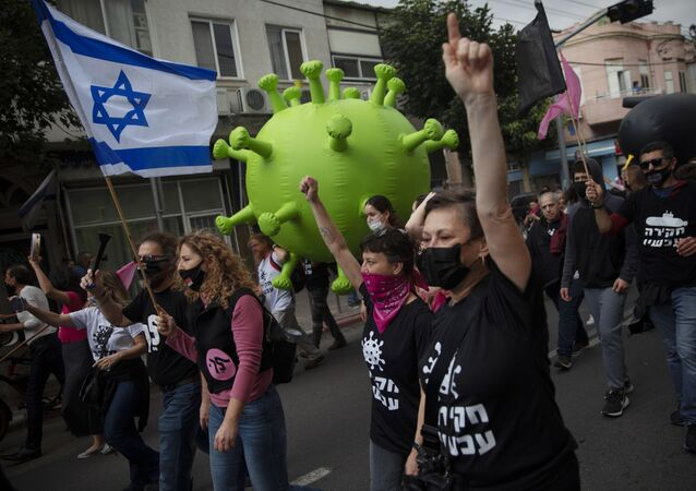 Israeli protesters march with a large inflatable model of the coronavirus during a demonstration against Israeli Prime Minister Benjamin Netanyahu in Tel Aviv, Israel, Friday, Feb. 5, 2021.