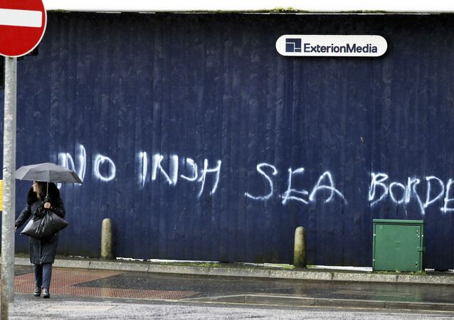 A woman walks past past graffiti with the words 'No Irish Sea Border' in Belfast city centre, Northern Ireland, Wednesday, Feb. 3, 2021