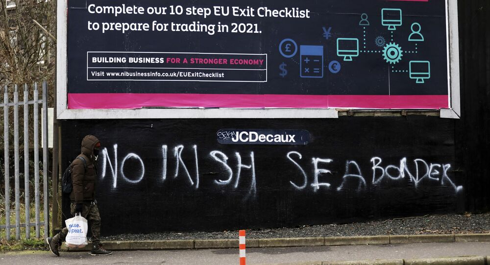 A man walks past graffiti reading No Irish sea border in the mainly loyalist Donegal road area of South Belfast, Northern Ireland, Saturday, 30 January 2021.