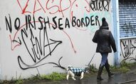 A woman walks her dog past past graffiti with the words 'No Irish Sea Border' in Belfast city centre, Northern Ireland, Wednesday, Feb. 3, 2021